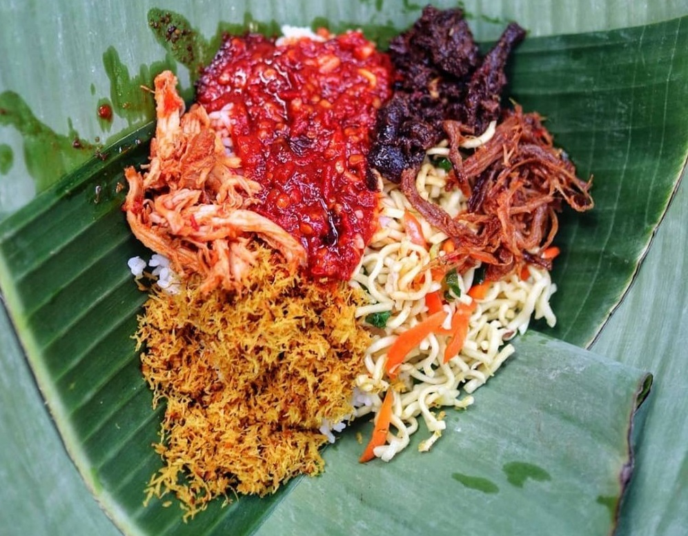 jinggo rice is served in a banana leaf wrapper with side dishes and condiment