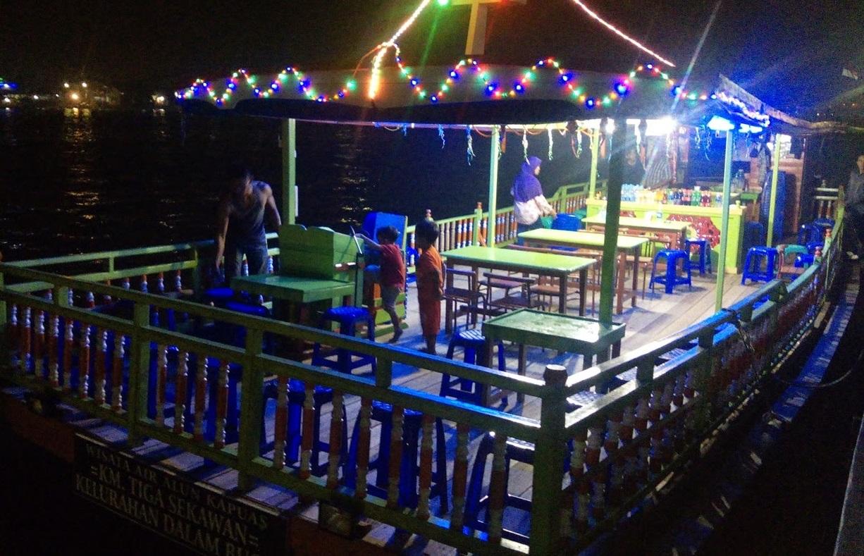 cruising kapuas river at night on tourist ship