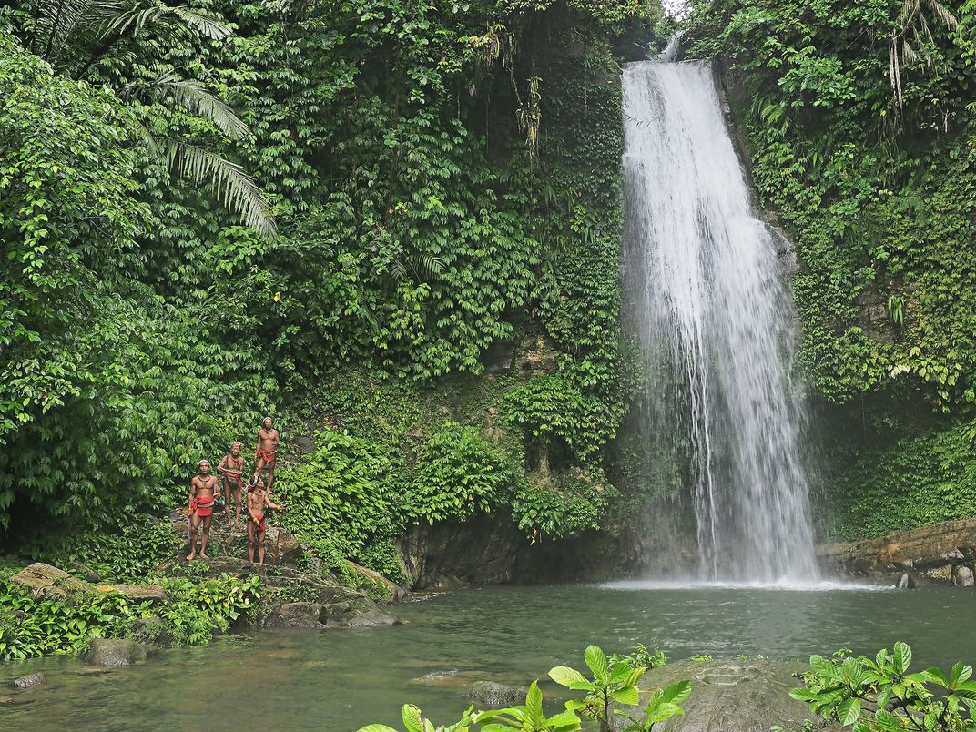 mentawai tribe in kulukubuk waterfall in siberut